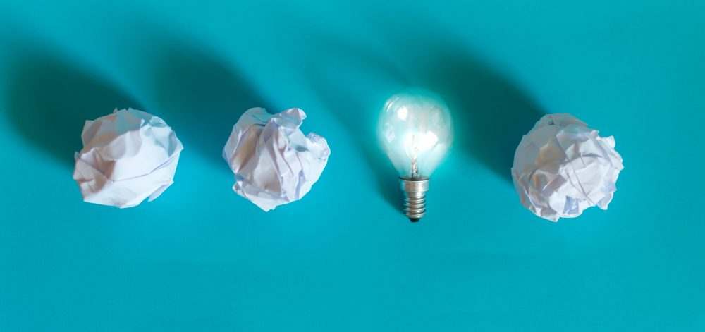 Concept of bright idea with paper and light bulbs. Business creativity, leadership concept.
